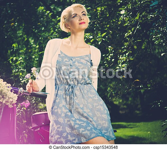 Beautiful blond woman sitting on a retro roller  - csp15343548