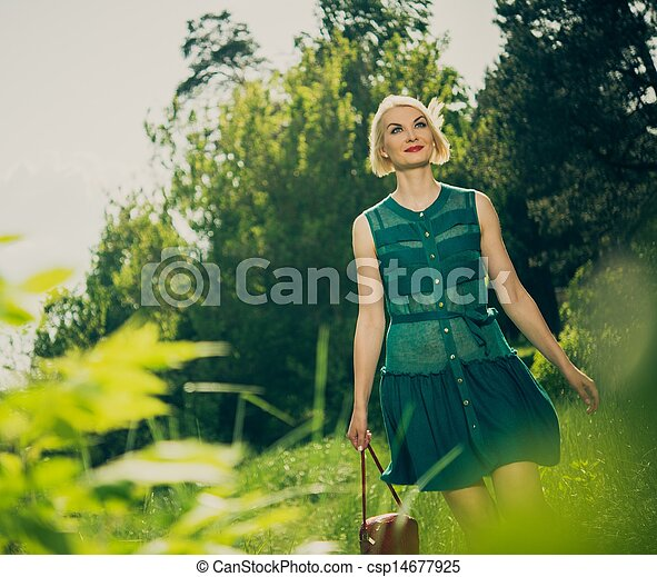 Beautiful blond woman with red bag in green dress outdoors - csp14677925