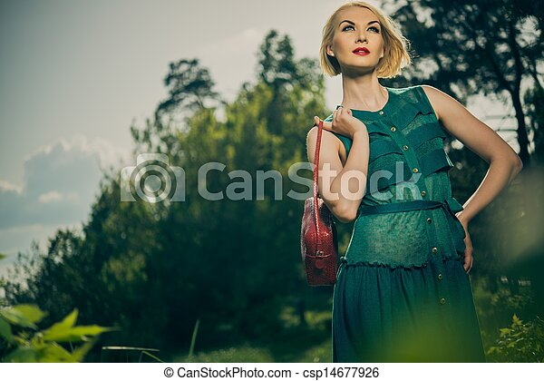 Beautiful blond woman with red bag in green dress outdoors - csp14677926