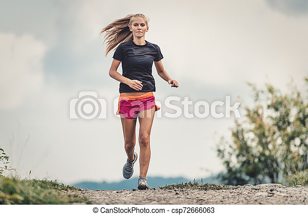Beautiful blonde athlete runs on dirt road in the hills - csp72666063