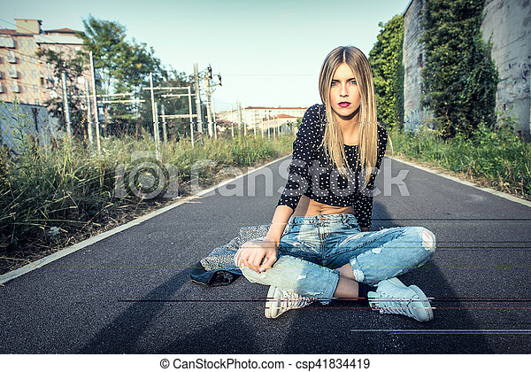 Beautiful blonde girl sitting on the street in town - csp41834419