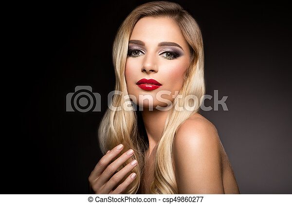 Beautiful blonde model girl with long curly hair . Hairstyle wavy curls . Red lips. - csp49860277