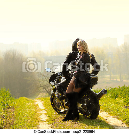 Beautiful blonde with a biker posing near a sports bike beautiful couple with a motorcycle at stock photo