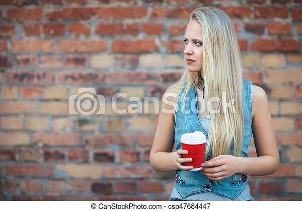 Beautiful blonde woman holding cup of coffee on brick wall background - csp47684447