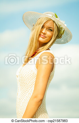 Beautiful blonde woman in hat on beach, summertime - csp21587983