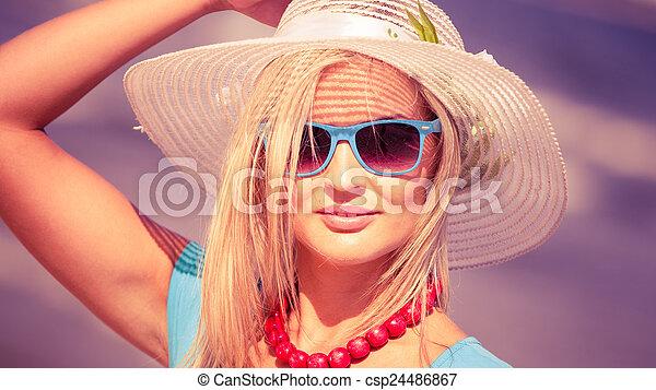 Beautiful blonde woman in hat on beach - csp24486867
