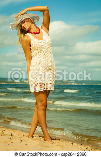 Beautiful blonde woman in hat on beach, summertime - csp26412366
