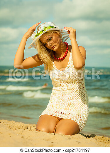 Beautiful blonde woman in hat on beach, summertime - csp21784197