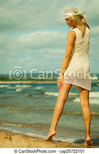 Beautiful blonde woman in hat on beach, summertime - csp25722101