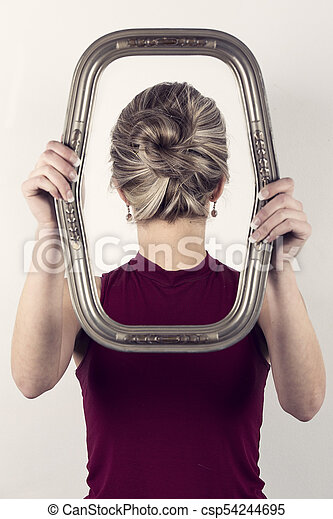 Beautiful blonde woman in red top holding a portrait frame in front of face looking backward - csp54244695