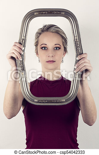Beautiful blonde woman in red top holding a portrait frame in front of face - csp54042333
