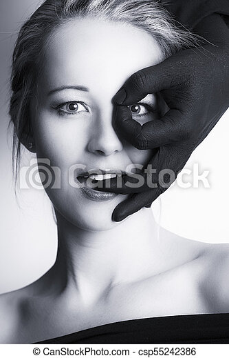 Beautiful blonde woman looking through fingers of black hand on her face artistic conversion - csp55242386