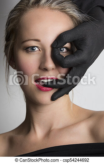 Beautiful blonde woman looking through fingers of a black hand on her face - csp54244692