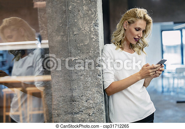 Beautiful blonde woman texting on phone - csp31712265