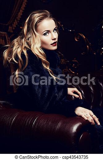 Beautiful blonde in fur coat curiously