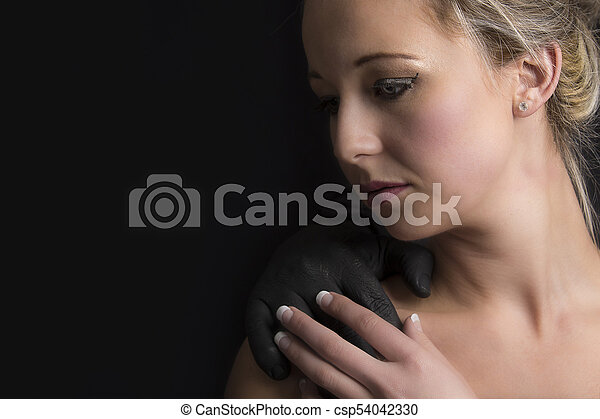 Beautiful blonde woman with a black hand of man on her shoulder - csp54042330
