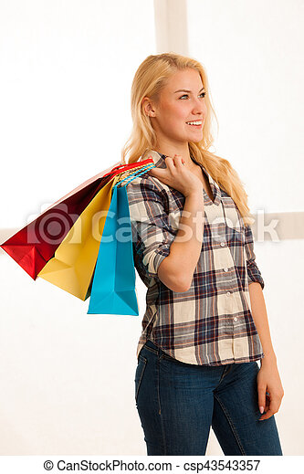 Beautiful blonde woman with long hari  holding shopping bags after purchase in a mall - csp43543357