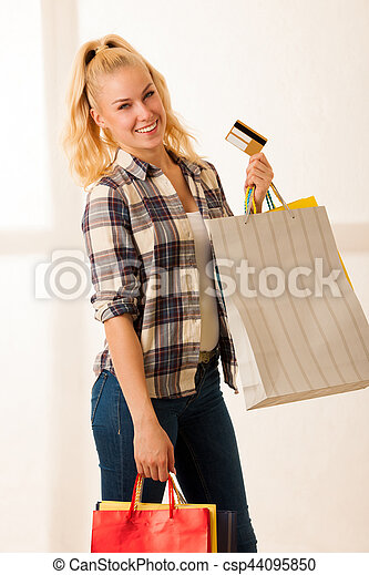 Beautiful blonde woman with long hari  holding shopping bags after purchase in a mall - csp44095850