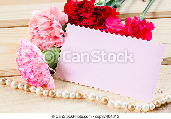 Beautiful blooming carnation flowers with blank pink card paper on beautiful blooming carnation flowers with blank pink card paper on wooden background ready for your text or message mightylinksfo
