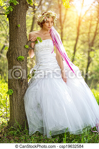 Beautiful bride  relying on tree - csp19632584