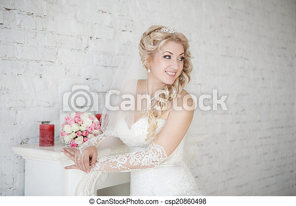 beautiful bride with wedding bouquet standing near fireplace - csp20860498