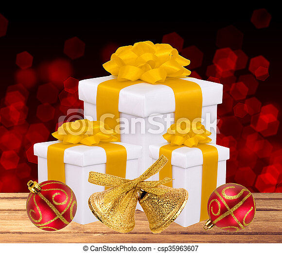 Beautiful bright gifts and Christmas decoration on wooden table over bokeh background - csp35963607