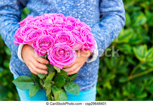 Beautiful bright pink roses in child's hands - csp29648401