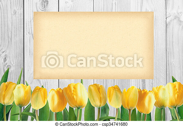 Beautiful bright yellow tulips on wooden background and empty paper card - csp34741680