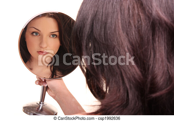Beautiful brunette looking in mirror on white - csp1992636