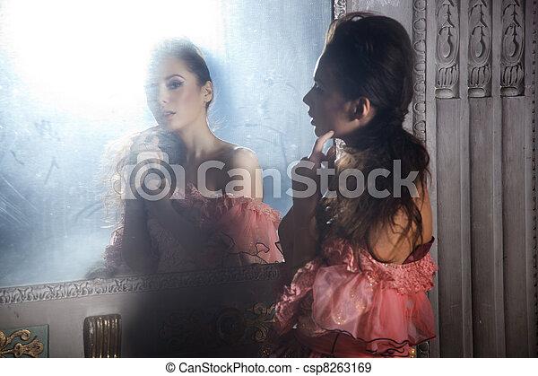 Beautiful brunette standing next to a mirror - csp8263169