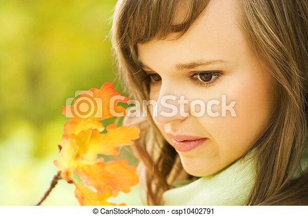 Beautiful brunette with autumn leaves close-up portrait - csp10402791