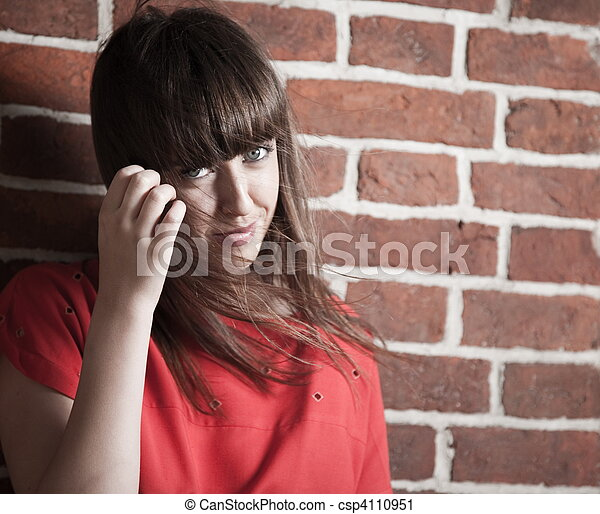 Beautiful brunette woman in front of a brick wall - csp4110951