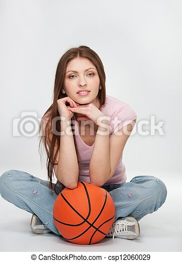 Beautiful brunette woman with a orange ball. - csp12060029