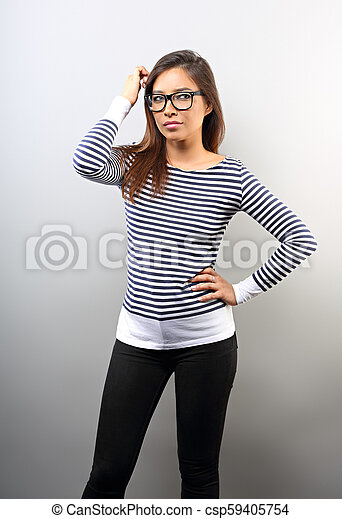 Beautiful business serious woman in glasses looking and scratched the head with thinking look on empty space background. - csp59405754