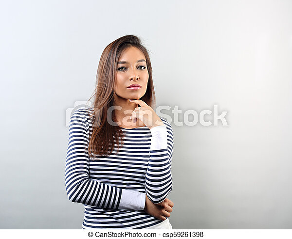 Beautiful business woman thinking and looking serious on blue background with empty copy space - csp59261398