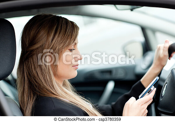 Beautiful businesswoman sending a text while driving  - csp3780359