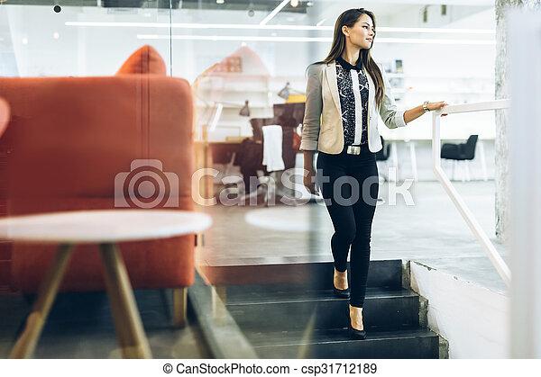 Beautiful businesswoman walking down the stairs - csp31712189