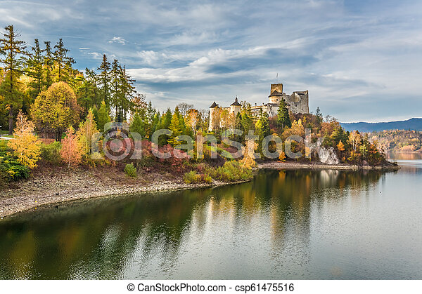 Beautiful castle by the lake at dusk in autumn - csp61475516