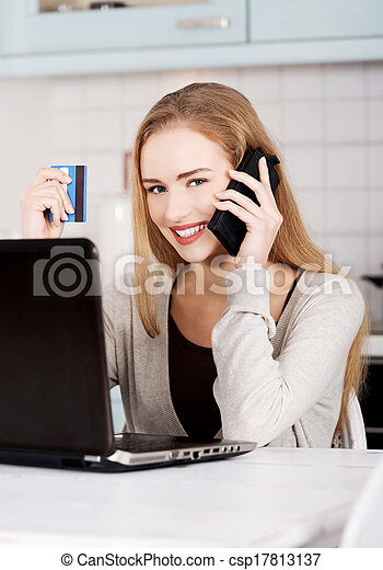 Beautiful caucasian woman talking through phone and working with laptop. Indoor background. - csp17813137