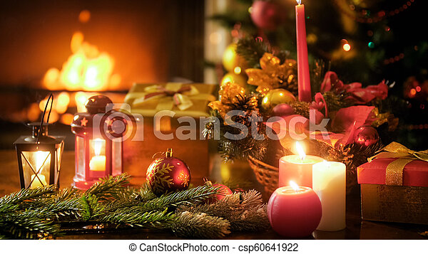 Beautiful Christmas Background.Beautiful Christmas Background With Candles And Lanterns On Wooden Table Against Burning Fireplace
