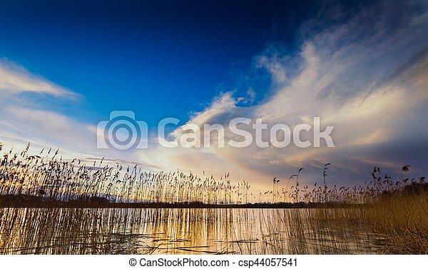 Beautiful cloudy sky over lake at sunset - csp44057541