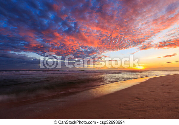 Beautiful colored clouds at the beach at sunset - csp32693694