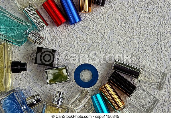 beautiful colored glass bottles with perfume on a gray surface - csp51150345