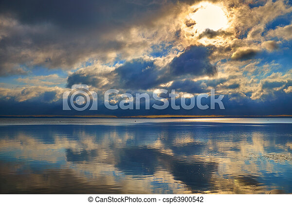 beautiful colourful sunrise over the smooth surface of a lake - csp63900542