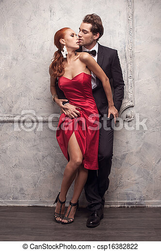 Beautiful couple in classical outfits. Standing and kissing with passion  - csp16382822