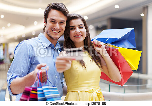 Beautiful couple showing credit card in the shopping mall  - csp13978188
