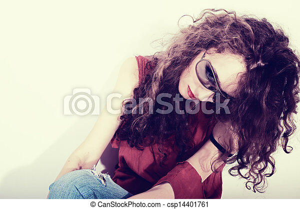 beautiful curly brunette woman in red T-shirt and blue jeans - csp14401761