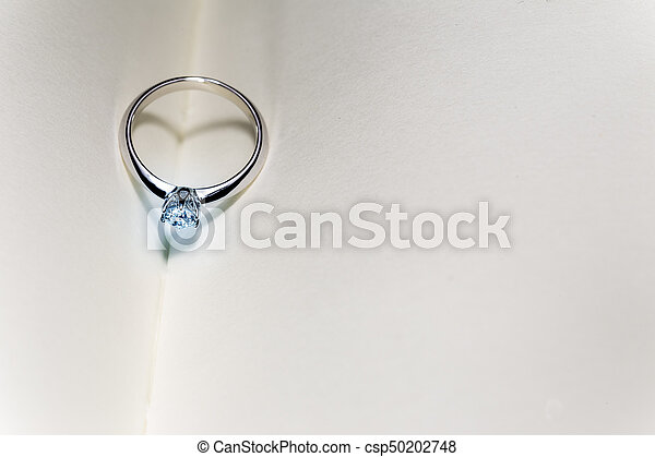 beautiful diamond ring on blank open book with heart shape shadow