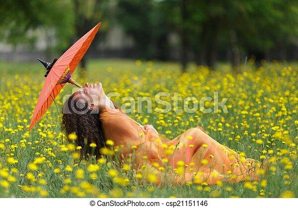 Beautiful elegant woman with an orange parasol - csp21151146