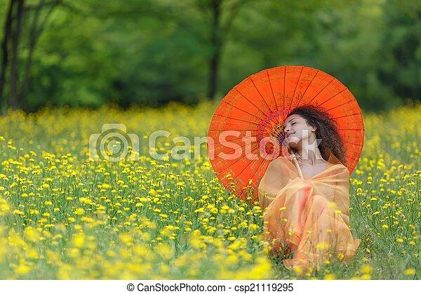 Beautiful elegant woman with an orange parasol - csp21119295
